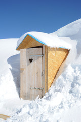 Wooden toilet box in the middle of snow