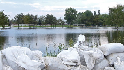 Flooded football field, in the foreground is a levee of sandbags