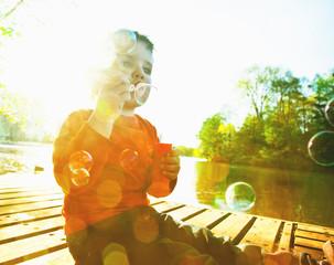 Little boy blowing soap bubbles at a lake