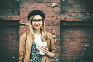 stylish woman drinking coffee on brick wall background