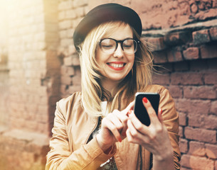 City lifestyle stylish hipster girl using a phone texting on sma