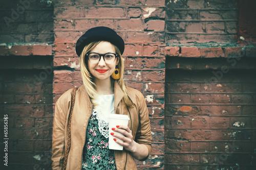 stylish woman drinking coffee on brick wall background - 65856365