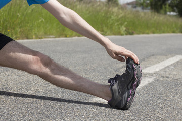Close-up of a jogger stretching his legs