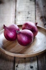 Red onion in wooden plate