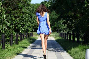 Young woman walking in summer park