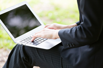 businesswoman using laptop computer in the park