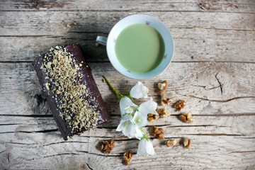 Chocolate swiss roll with walnuts and cup of green tea