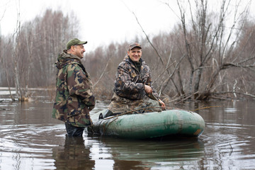 the hunters put stuffed ducks on water from a rubber boat