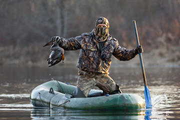 hunter with dead duck in a boat