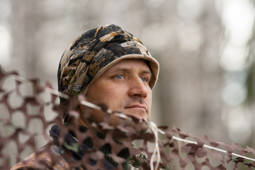 The hunter looks out from behind camouflage netting