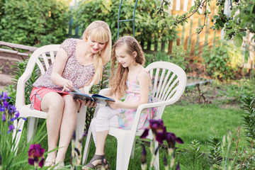 portrait of a beautiful young mother and her daughter reading bo