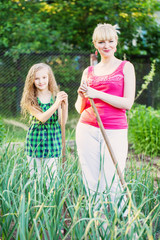 young girl with mother working in vegetable garden