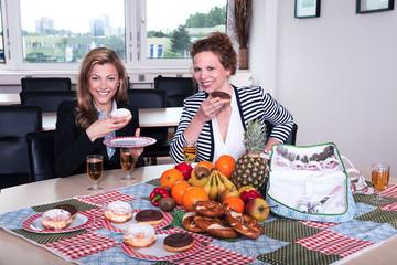 Geschäftsfrauen machen Picknick im Büro in der Pause