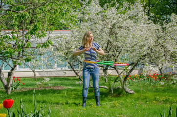 girl turning hula hoop between flowering cherry