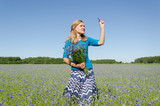 smiled woman pose in cornflower bent with bouquet