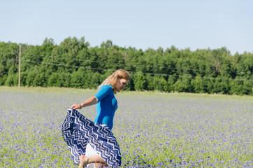 girl dance in endless cornflower meadow in summer