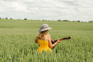 Country girl in dress play guitar wheat field
