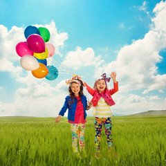 Children with balloons walking on summer field
