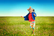 Cute little girl running on meadow in a field