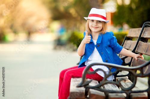Portrait of little girl in a park showing thumb up