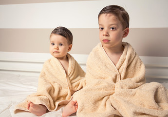 Sweet boy and little girl under towels over a bed