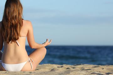 Woman meditating yoga on the beach in summer