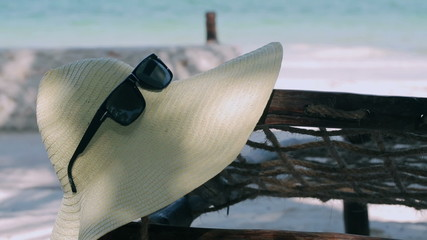 Hat and sunglasses hanging on the sunbed