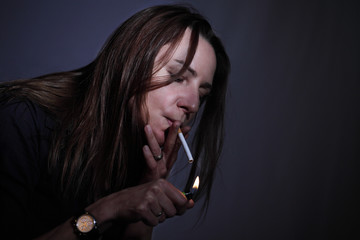 Smoking woman lighting a cigarette