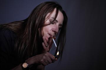 Smoking woman lighting a cigarette