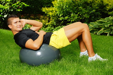 Young man working out in a garden with the fitness ball