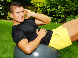 Young man exercises in a garden with the fitness ball