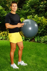 Young man in garden poses with the fitness ball