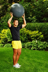 Young man in garden exercises with the fitness ball overhead