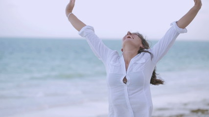 Happy woman rising hands and smiling on the beach, steadycam sho