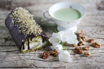 Swiss roll with matcha tea and chocolate icing filled with cream