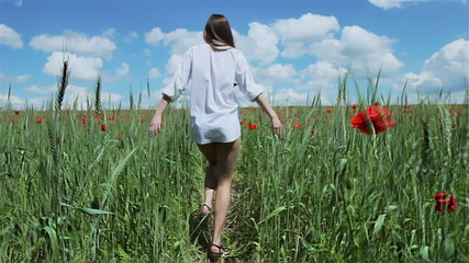 Topless woman running in poppy field
