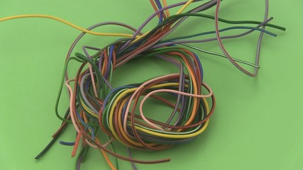 Multicoloured six amp electrical wire on a green background.