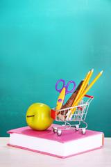 School supplies in supermarket cart on blackboard background