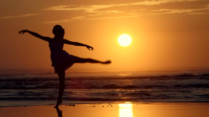 Silhouette of woman dancing Ballet on Beach at Sunset