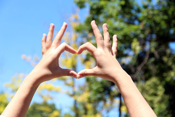 Young girl holding hands in heart shape framing