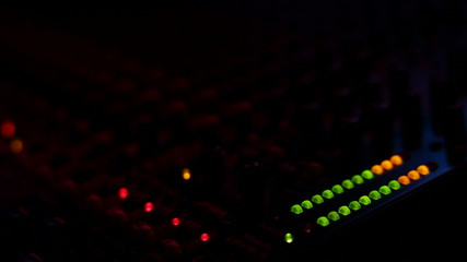 Mixing board at a concert with red and blue light turning on and