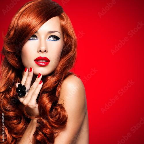 Beautiful sensual woman with long red hairs.