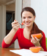 girl in red eats grapefruit at home