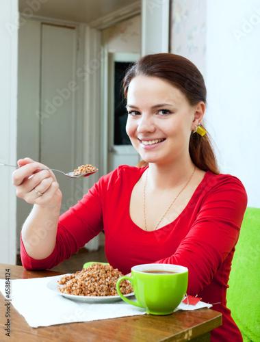 Happy girl eats buckwheat