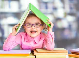 Little girl in glasses under roof made from book.