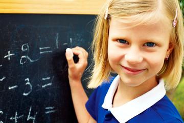 schoolgirl decides on a blackboard mathematical tasks