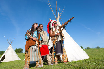 Three North American Indians stand near a wigwam