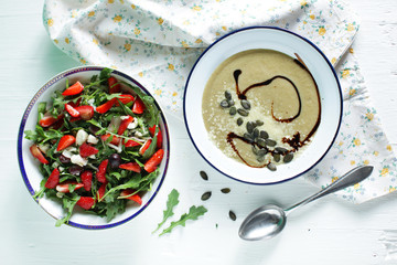 Arugula salad with strawberries and eggplant creamy soup