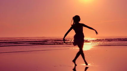SIlhouette of girl dancing on Beach at sunset