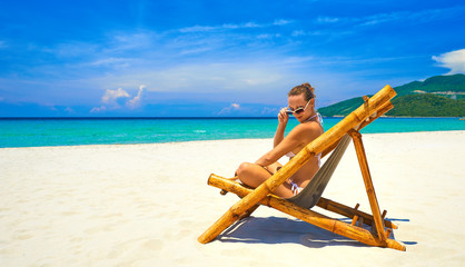 Happy attractive young  woman in bamboo chair at the beach